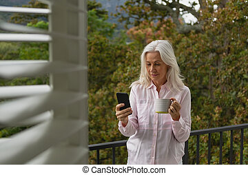 Woman using mobile phone while holding coffee mug on the balcony