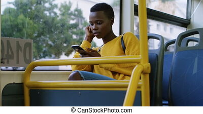 Woman using mobile phone while travelling in bus 4k - Young...