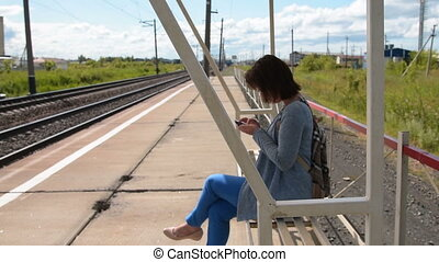 Woman using mobile while waiting for commuter train on the platform