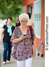 Woman Using Mobilephone On Pavement - Senior woman using...