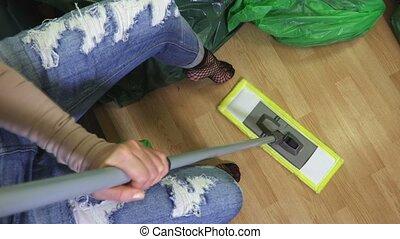 Woman using mop on floor in room