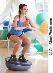 Woman Using On Balance Trainer At Gym