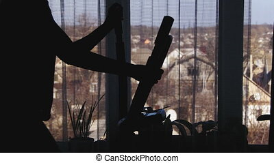 Woman Using on the Elliptical Trainer Cross Trainer at Home on Against the Window.