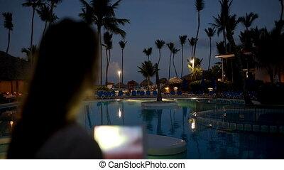 Woman using pad to take photos on tropical resort