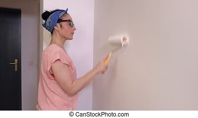 Woman using paint roller brush