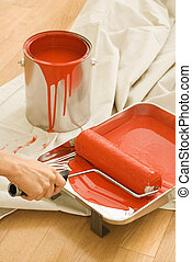 Woman using paint roller. - Hand holding paint roller in...