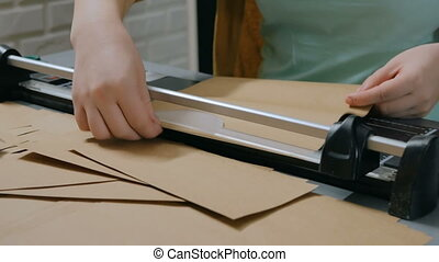 Woman using paper cutter, guillotine