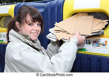 Woman using paper recycling bin
