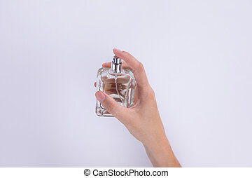 Woman using perfume on a white background