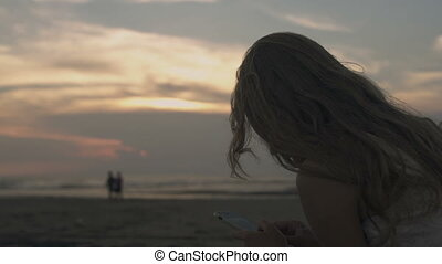 woman using phone at the beach