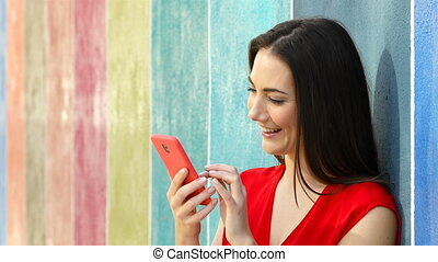 Woman using phone in a colorful wall - Happy woman using...