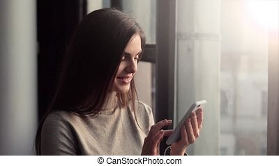 Woman Using Phone near Window