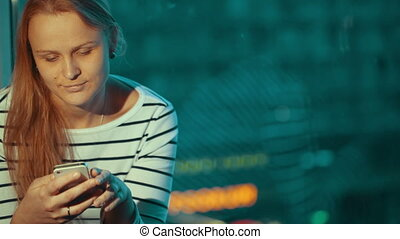 Woman using phone sitting by the window in the evening