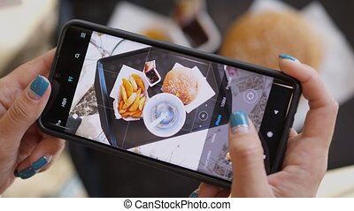 Woman using phone to take pictures of Burger, french fries and cola. Tourist girl have brunch or lunch time at fast food cafe