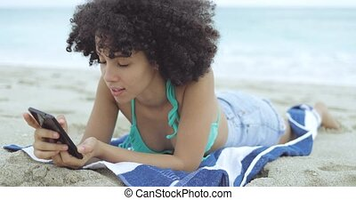 Woman using phone while chilling on sand