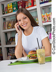 Woman Using Phone While Having Snacks In Store