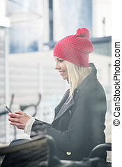Woman using phone while waiting for a suburban train