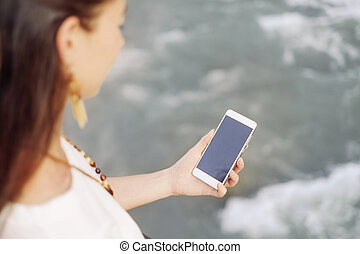 Woman using phone while walking near the river.