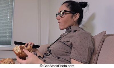 Woman using remote control and eating bun