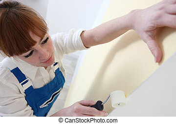 Woman using roller to paste wallpaper to wall