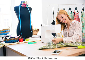 Woman using sewing machine - Pretty young woman using sewing...