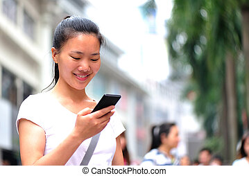 woman using smart phone on street