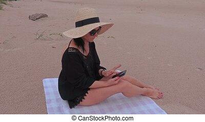 Woman using smart phone on the beach near sea