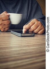 Woman using smart phone with coffee cup