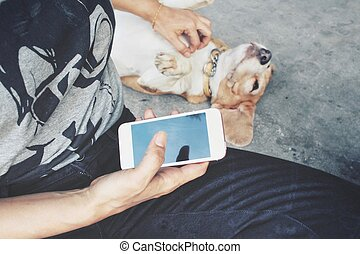 Woman using smart phone with dog