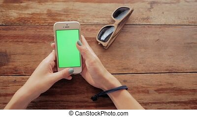 woman using smart phone with green screen on wooden table background