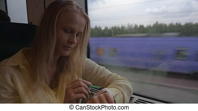 Woman using smart watch during train ride - Young blond...