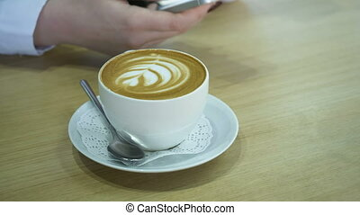 Woman using smartphone and drinking cappuccino. - Young...