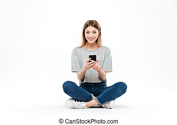 Woman using smartphone and sitting on floor