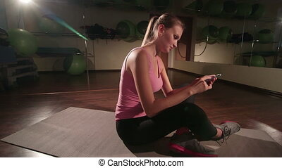 Woman using smartphone application to build custom routine in gym crane shot