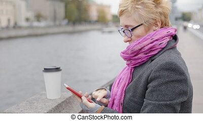 Woman using smartphone at river - Adult woman in glasses...