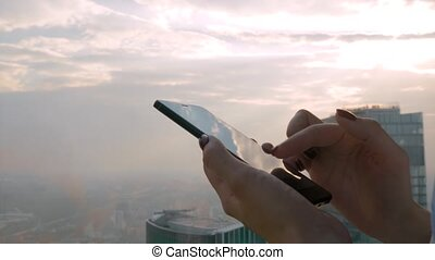 Woman using smartphone device against cityscape view - close up side view