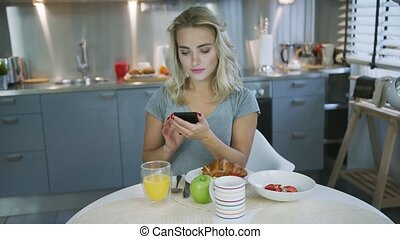 Woman using smartphone during breakfast - Beautiful young...