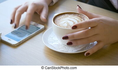 Woman using smartphone during coffee break.