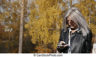 Woman using smartphone in autumn park