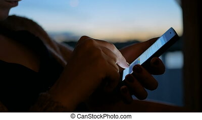 Woman using smartphone in cabin of cruise ship. Evening...