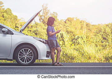 Woman using smartphone in front of her broken car on the road. Contacting car technician or need help concept