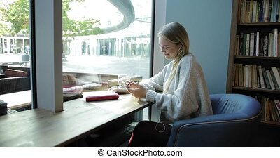 Woman using smartphone in front window - Pretty young woman...