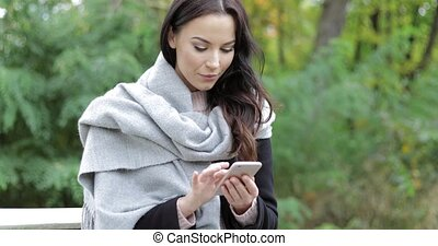 Woman using smartphone in park - Attractive woman in black...
