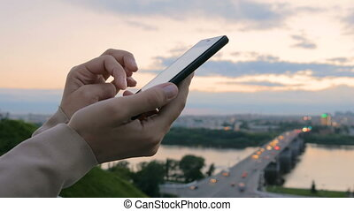 Woman using smartphone in the city after sunset