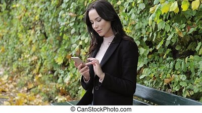 Woman using smartphone on bench - Woman in black jacket and...