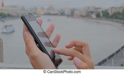 Woman using smartphone on embankment - close up shot -...
