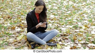 Woman using smartphone on grass