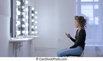 Woman using smartphone sitting in front of mirror