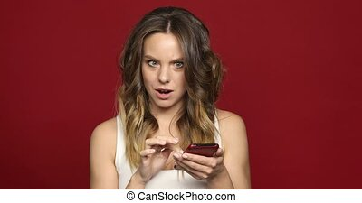 Woman using smartphone strange news - Young woman using her...