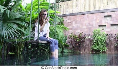 Woman using smartphone while sitting on swing near pool in tropical country.